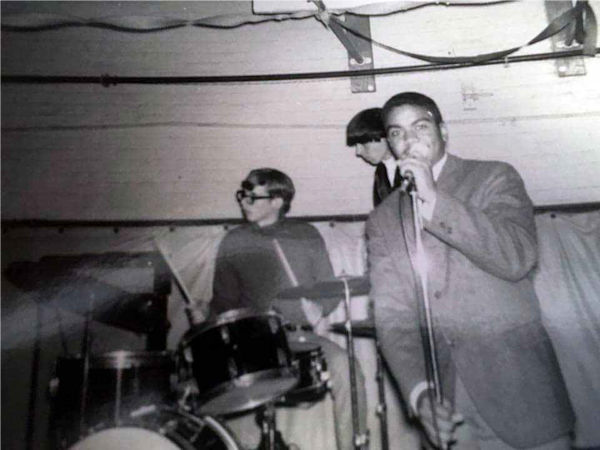 Setting up before a Younger Generation performance at Oyster Bay High School gymnasium. Left to right, Bob Levitan (at drums), Alan Galasso, Joe Tolliver at microphone (roadie)